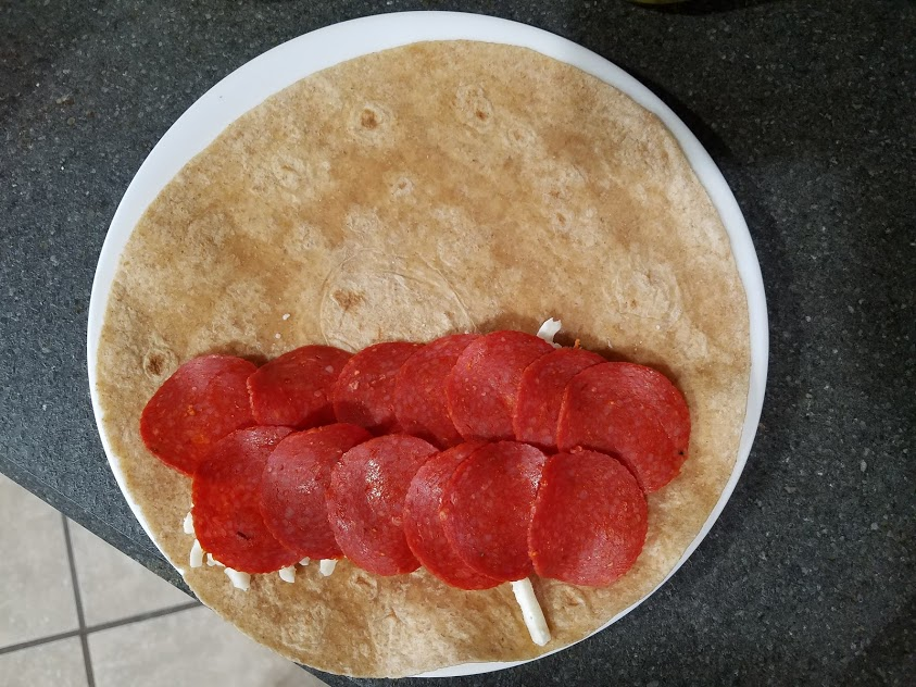 Image of a tortilla topped with pepperoni and mozzarella cheese