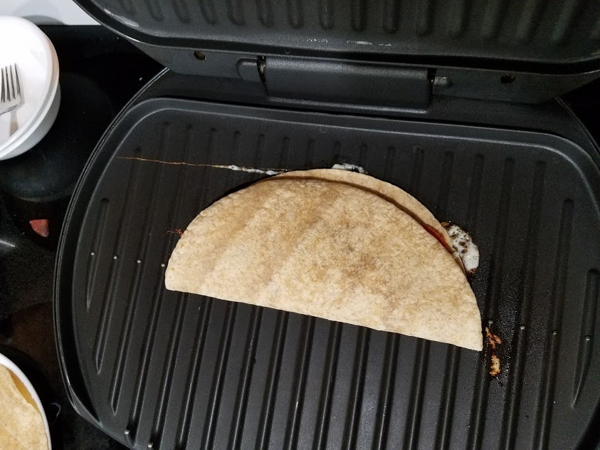 Image of a quesadilla cooking on a George Foreman grill