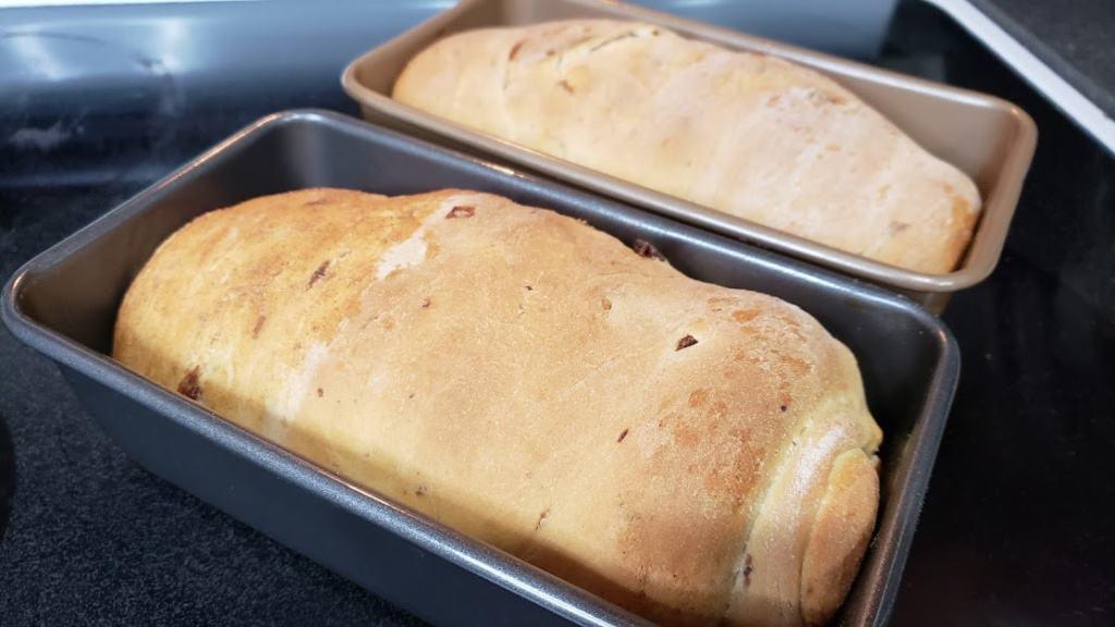 Two loaves of cinnamon raisin bread in bread pans
