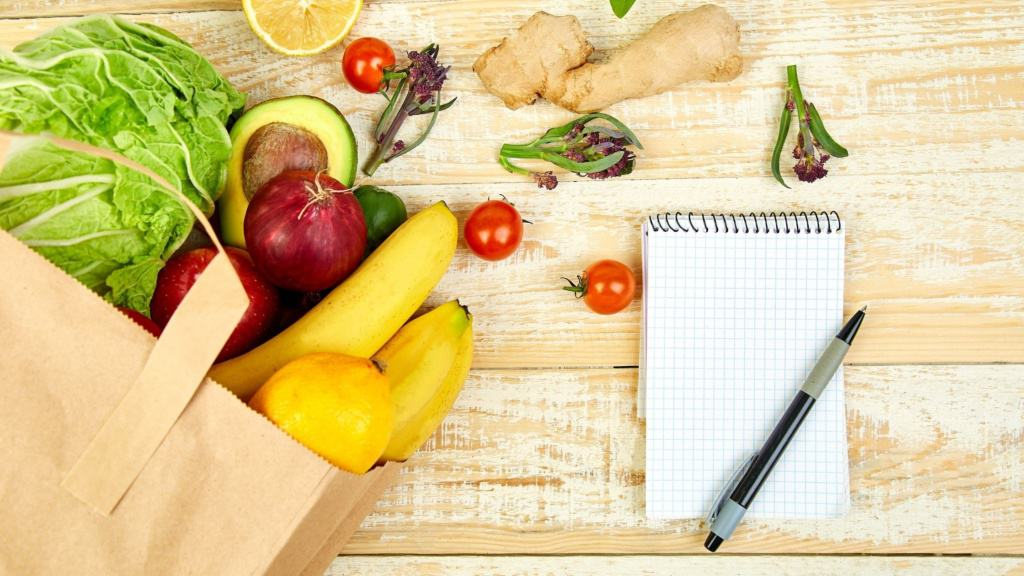 Image of a bag of groceries on a table, with a notebook and a pen