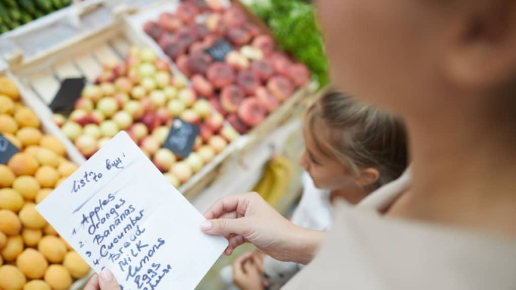 Image of a mom and daughter at a grocery store. The mom is holding a grocery list.
