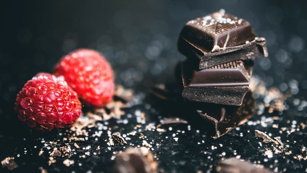 Image of chocolate squares next to two raspberries