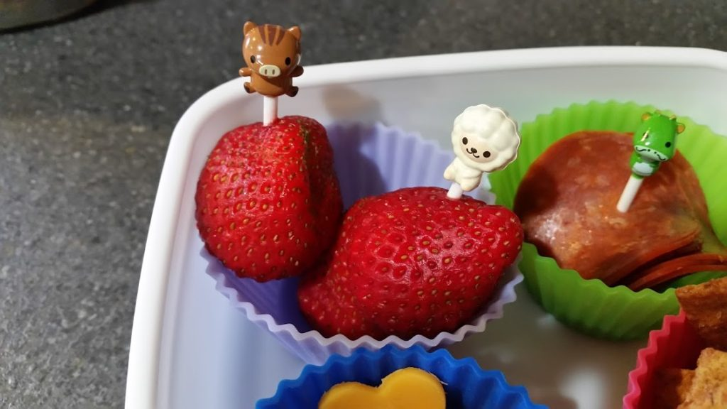 Image of a lunchbox with food picks stuck into strawberries