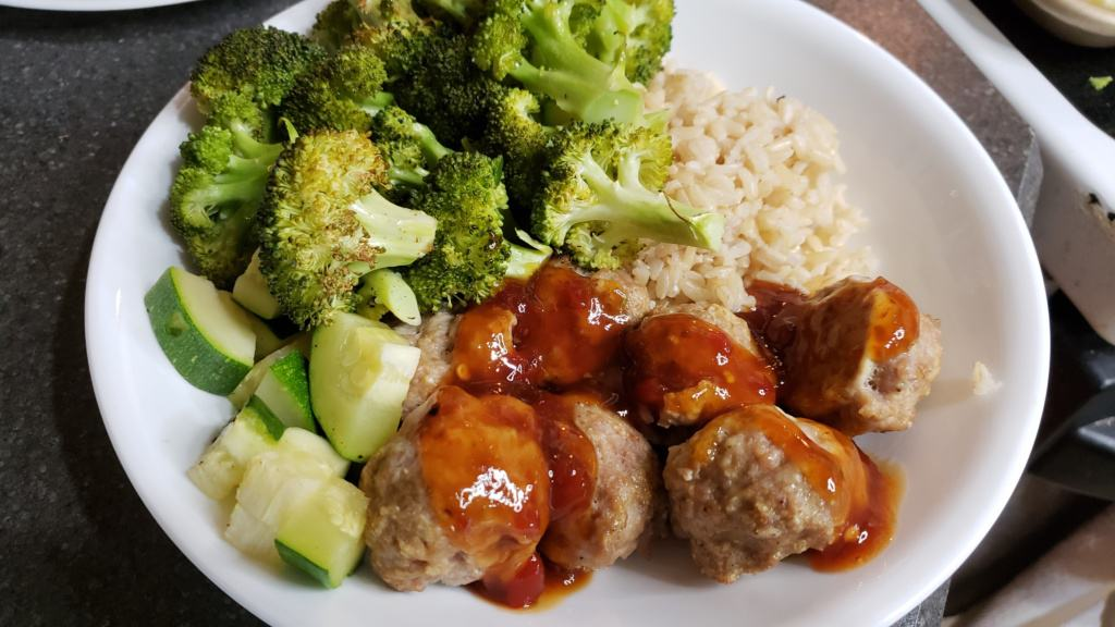 A bowl of meatballs, rice, broccoli, and zucchini