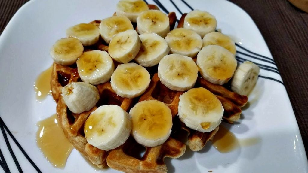 An image of a waffle on a plate topped with a sliced banana and syrup