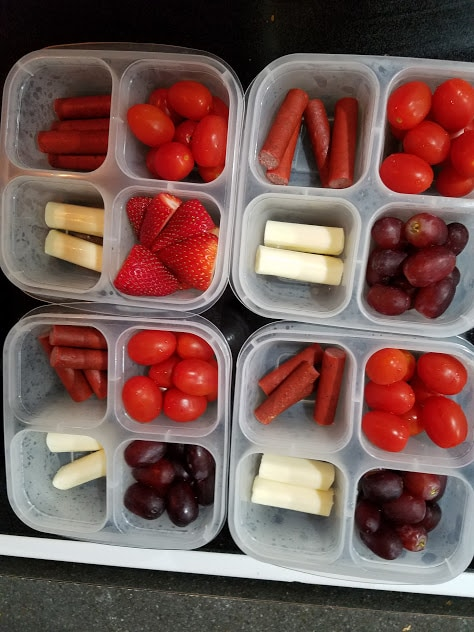 Image of 4 snack containers filled with grape tomatoes, strawberries, string cheese, and meat sticks