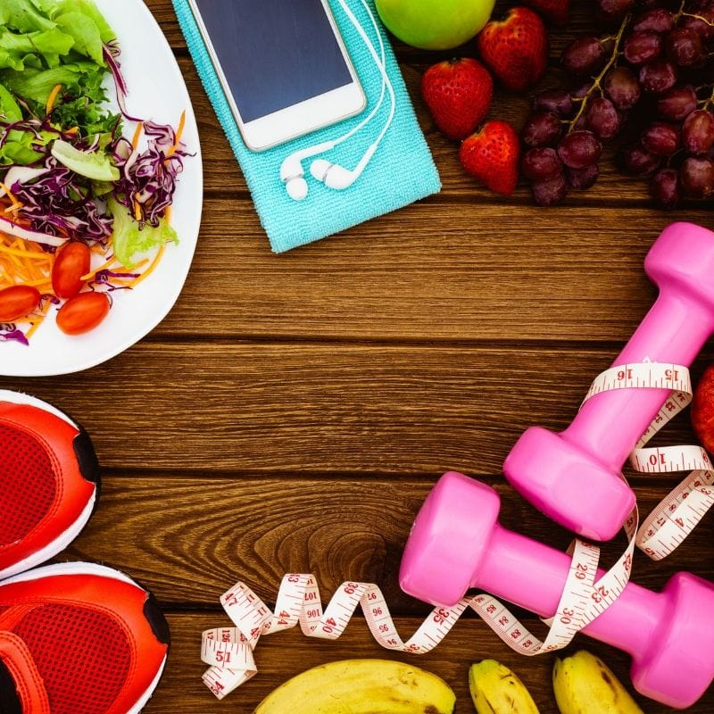 An image of healthy objects such as dumbbells, measuring tape, running shoes, and a salad and bananas
