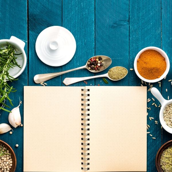A blank notebook surrounded by ingredients