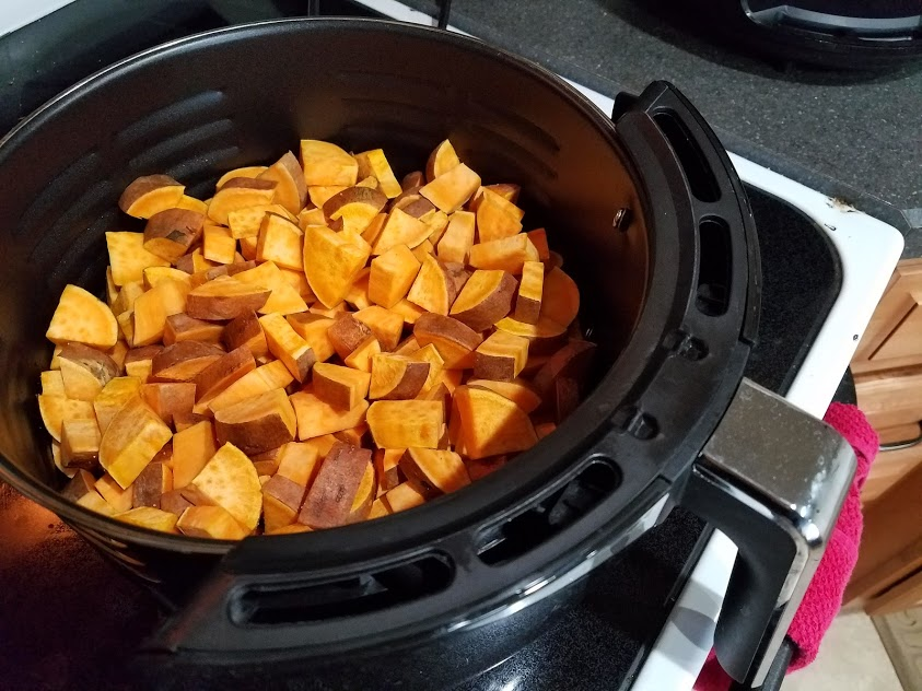 Image of chopped sweet potatoes in an air fryer basket