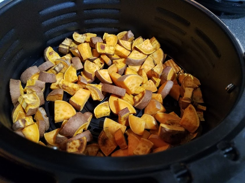 Image of cooked sweet potatoes in an air fryer basket