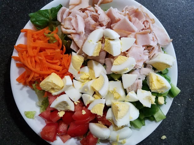 Image of a bowl of salad vegetables, hard boiled eggs, and deli ham
