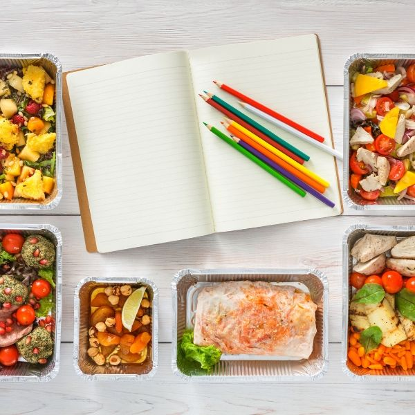 Image of a notebook topped with colored pencils, surrounded by containers of food