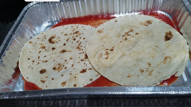 Image of a 9x13 pan with tomato sauce and tortillas