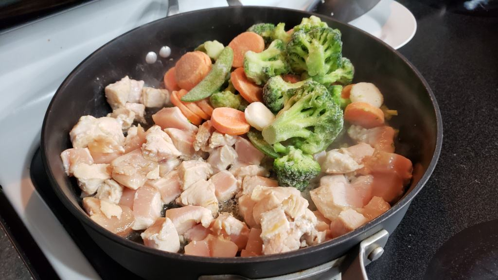 Raw cubed chicken and frozen vegetables cooking in a pan