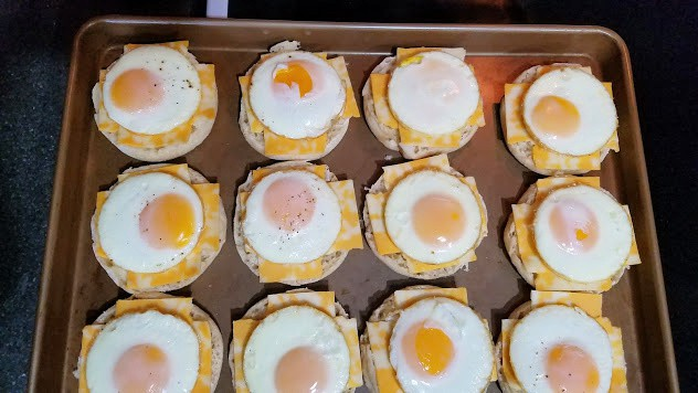 Image of English muffins with egg and cheese on top