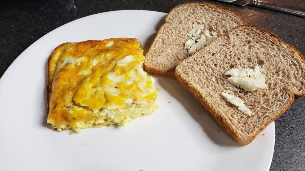 Egg casserole on a plate with toast and butter