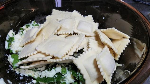 Image of a bowl filled with ravioli bake ingredients