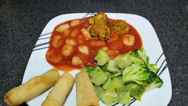 Image of cooked gnocchi with meatballs, broccoli, and spring rolls