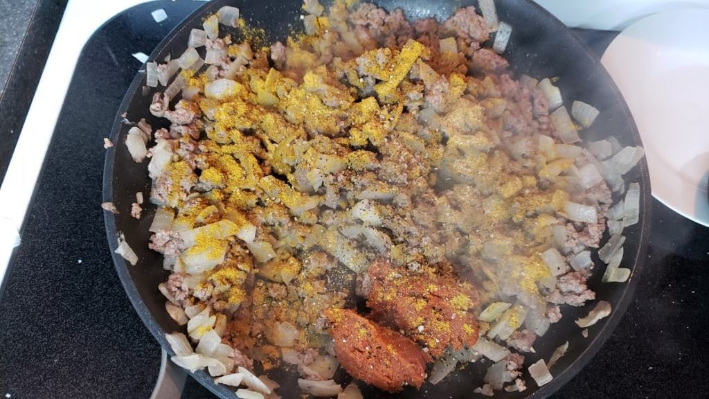 A skillet with ground beef, onions, and spices