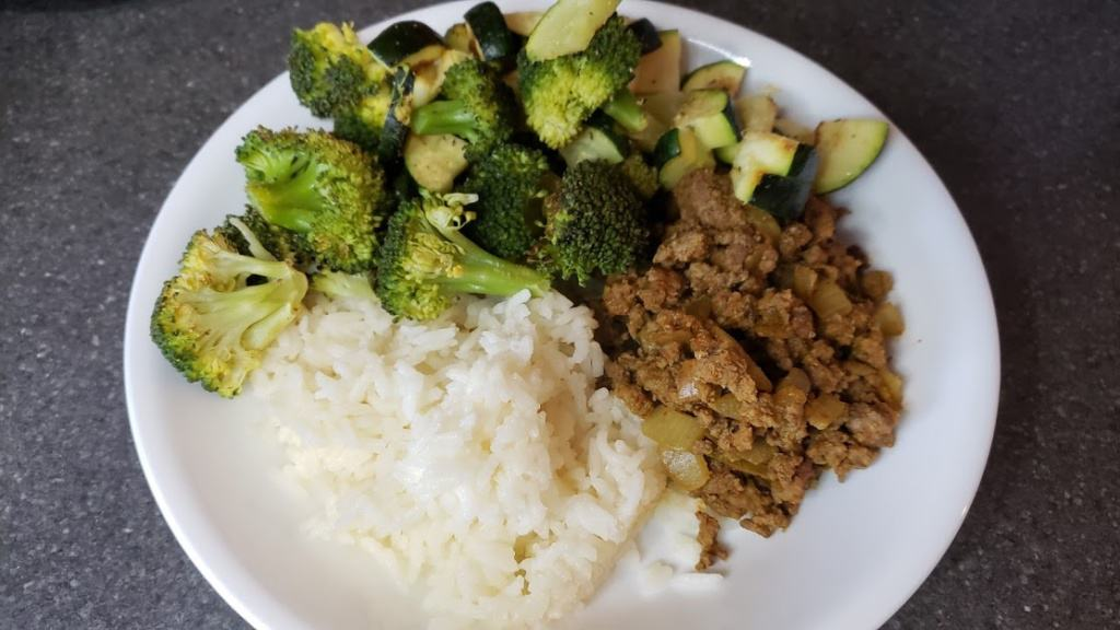 A bowl with ground beef, rice, and vegetables