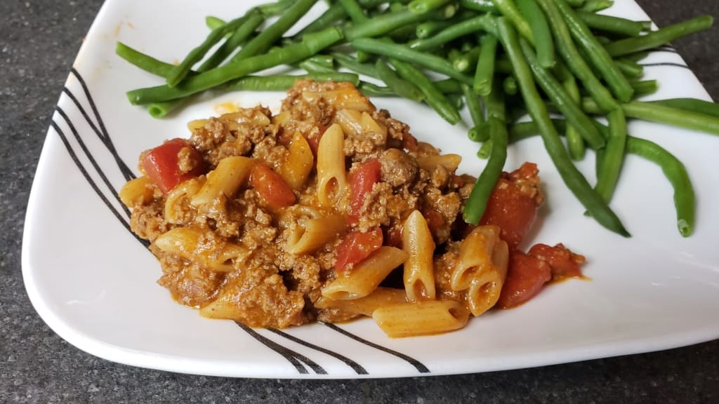 A plate containing a pasta skillet dish and green beans