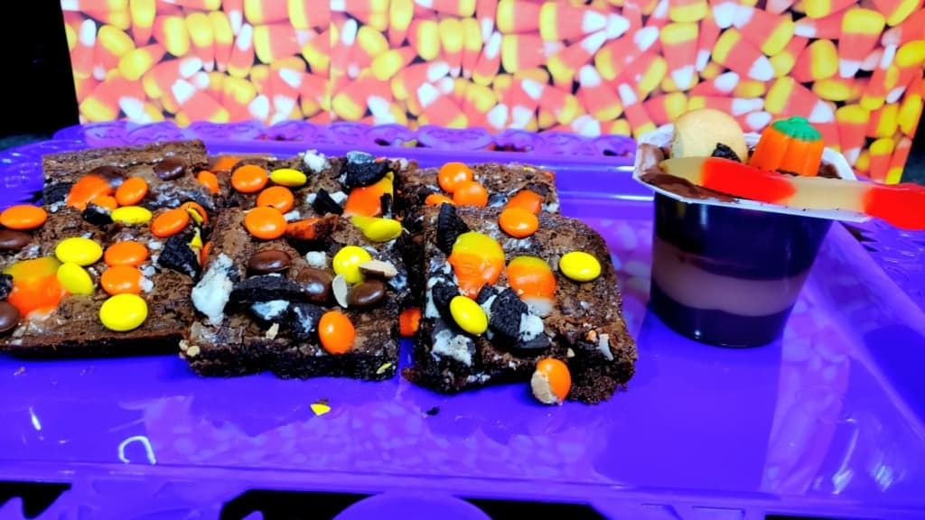 Halloween brownies and pudding cup on a purple tray