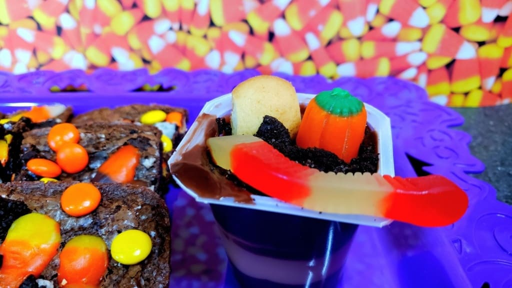 Finished pudding cup with crushed Oreos, vanilla wafer, candy pumpkin, and a gummy worm