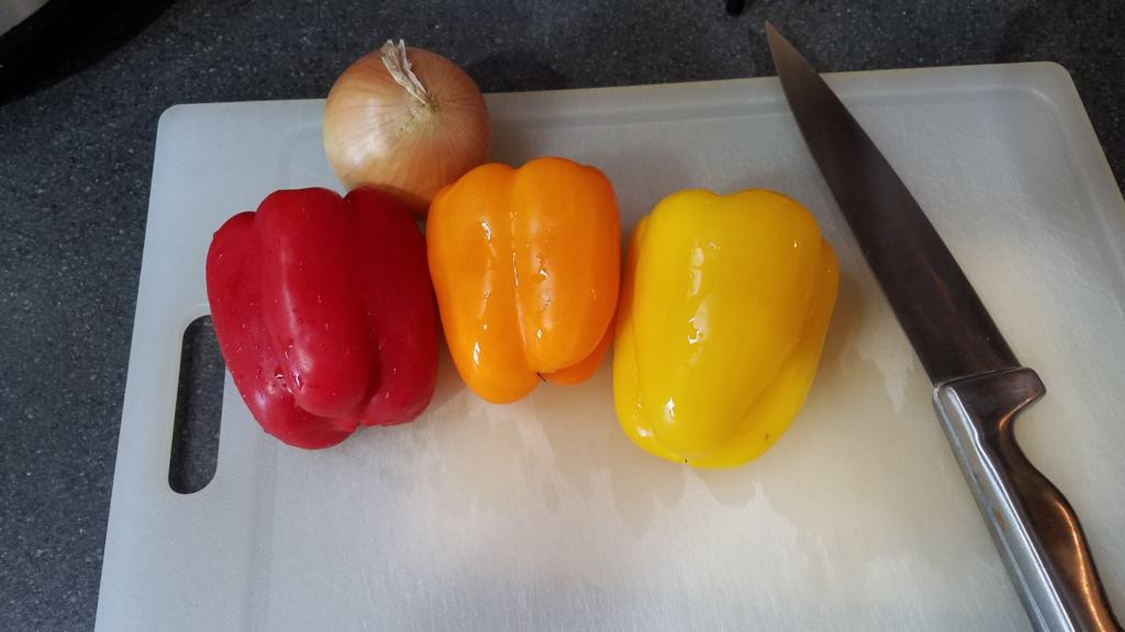 A cutting board with a red, yellow, and orange bell pepper, and an onion
