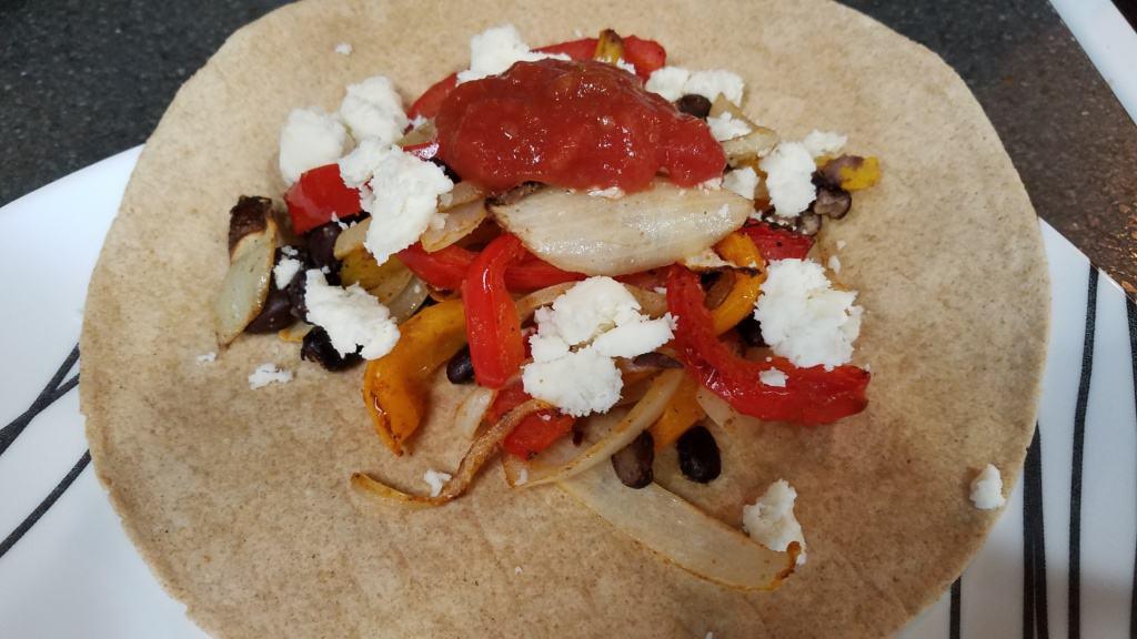 A plate with veggie fajitas on a tortilla