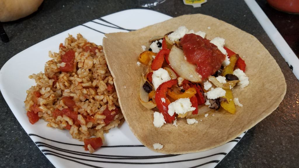 A plate with veggie fajitas on a tortilla, with Spanish rice
