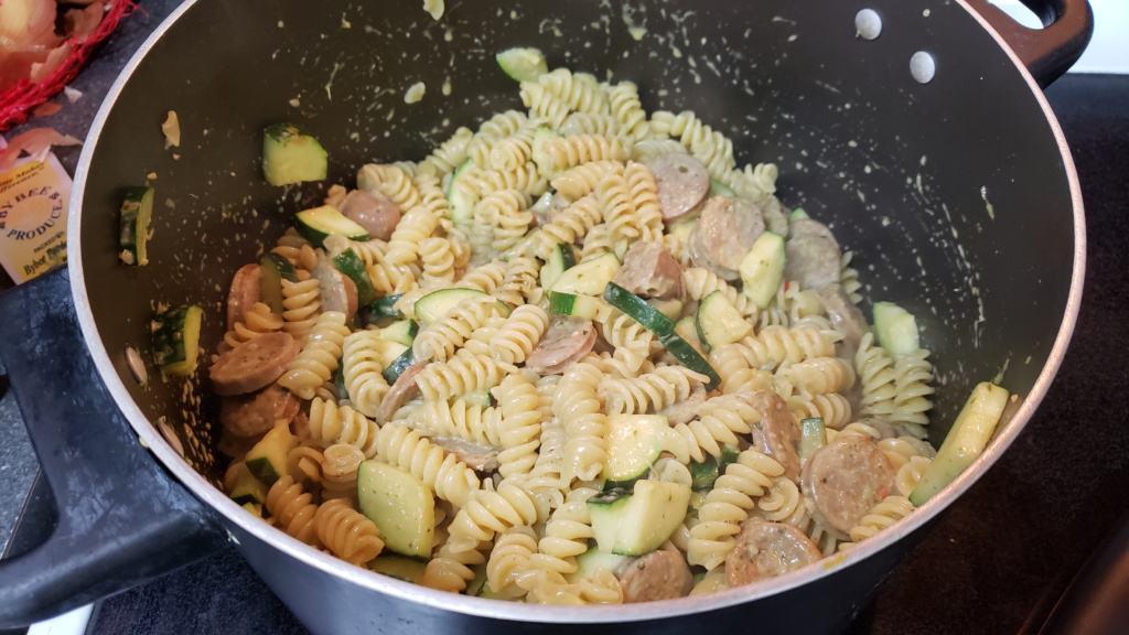 A large pot with mixed pasta and pesto mixture